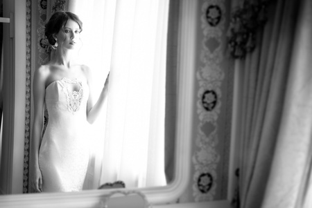 Beautiful bride in white wedding dress standing in her bedroom near the window Stock Photo