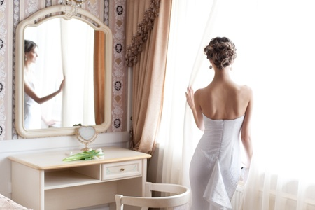 Beautiful bride in white wedding dress standing in her bedroom near the window photo