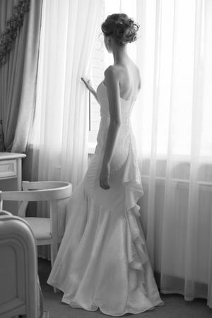 nude bride: Beautiful bride in white wedding dress standing in her bedroom near the window Stock Photo