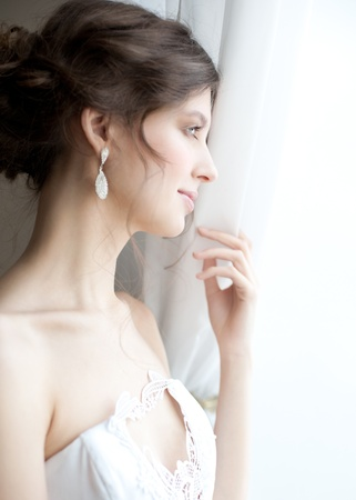 Beautiful bride standing near the window and looking away photo