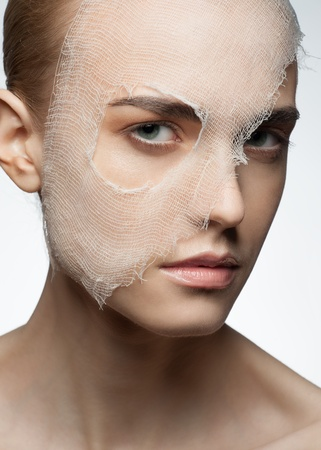 Portrait of young beautiful woman with bandage on her face. Woman having rejuvenation procedure photo