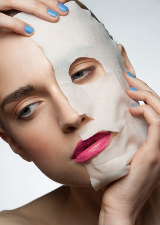 Portrait of young beautiful woman applying rejuvenating facial mask on her face photo