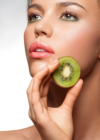 sexy food: Portrait of sensual young woman with stylish makeup holding delicious kiwi in her hand