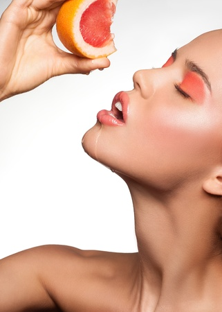 Portrait of sensual young woman with bright makeup holding delicious grapefruit in her hand photo