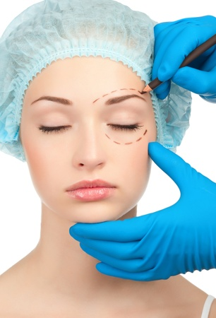 Beautician drawing perforation lines on woman face before plastic surgery operation Stock Photo - 13322261