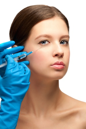 Cosmetic injection of botox to the pretty female face. Isolated on white background photo