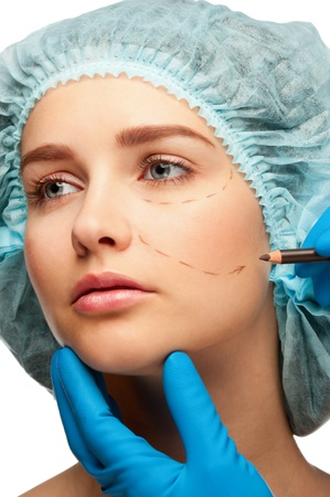 Beautician drawing perforation lines on woman face before plastic surgery operation. Isolated on white background photo