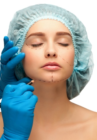 Beautician drawing perforation lines on woman face before plastic surgery operation photo