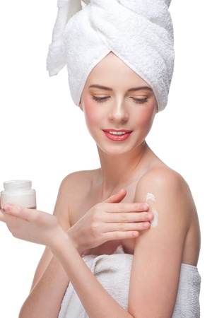 Young beautiful woman in white towel applying moisturizing cream on her shoulder. Isolated on white background photo