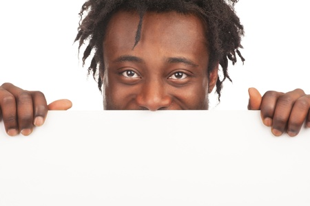 Cheerful young african american man with blank billboard peeking, isolated on white background photo