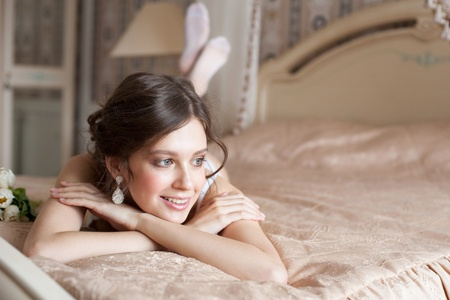 Beautiful woman lying on the bed in her bedroom photo