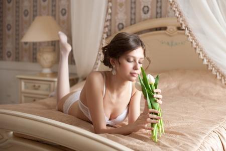 Bella sposa in lingerie bianco con bouquet di tulipani bianchi disteso sul letto nella sua camera da letto Archivio Fotografico - 13322568