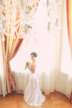 Beautiful bride in white wedding dress standing near the window indoors photo