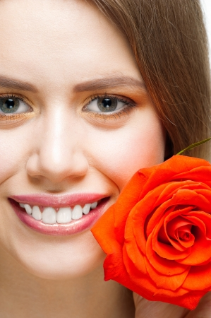 Close-up shot of pretty young woman with beautiful fresh make-up and perfect healthy skin with rose Stock Photo - 13644970