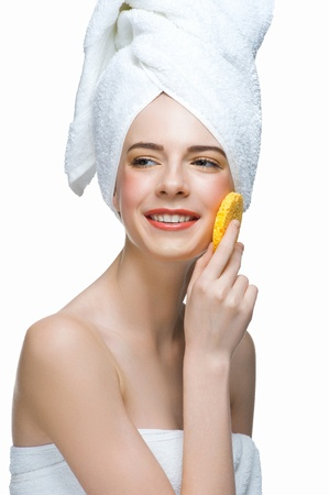 Portrait of young beautiful woman in white towel with bath sponge cleaning her face. Isolated on white background Stock Photo - 13644929