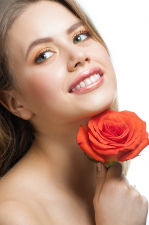 Pretty young woman with beautiful fresh make-up and perfect healthy skin with rose in her hands photo