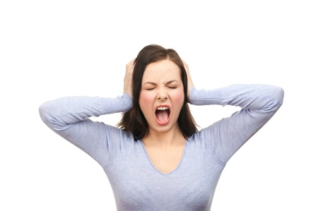 Portrait of a unhappy young woman covering her ears and screaming. Isolated on white background Stockfoto