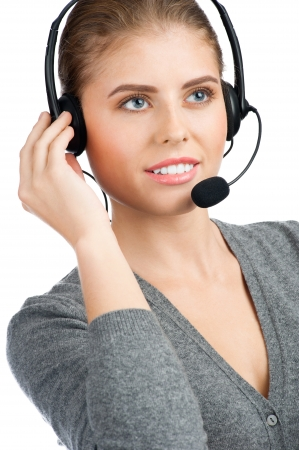 telephonist: Portrait of pretty female call center employee wearing a headset, against white background