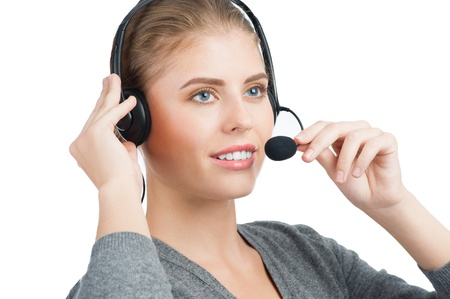 telephonist: Close-up portrait of a pretty female call center employee wearing a headset, against white background