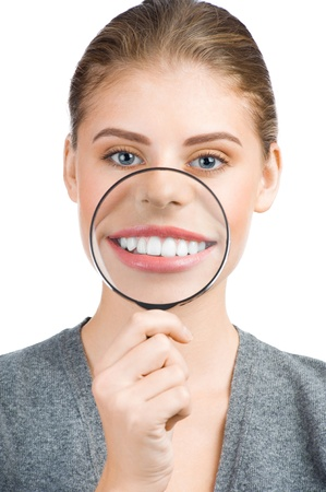 Portrait of lovely young woman with magnifying glass showing her white teeth photo