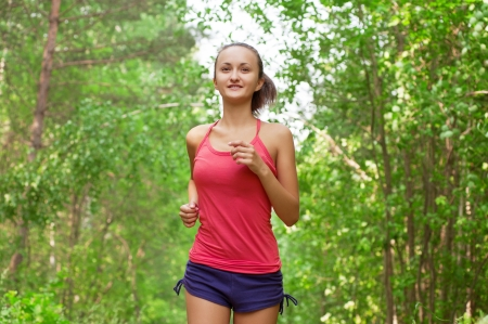 Young beautiful athlete woman jogging in park  photo