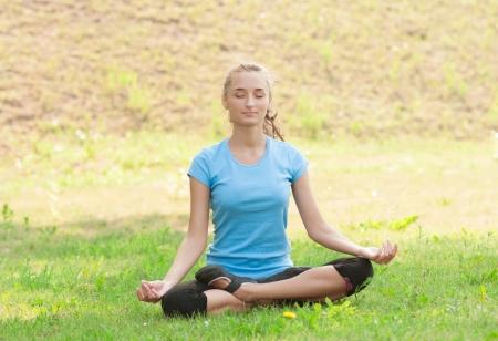 Young beautiful woman doing yoga meditation exercise outdoors photo