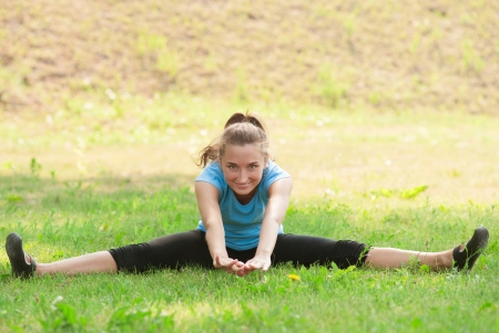 Young beautiful fitness woman doing sports stretching exercise outdoors photo