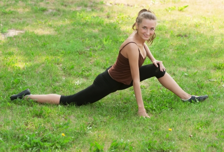 Young beautiful fitness woman doing sports stretching exercise outdoors