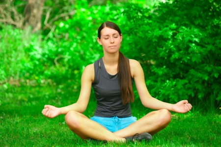 Young beautiful woman doing yoga meditation in forest outdoors photo