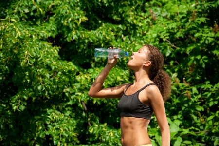 Young beautiful woman drinking water after fitness exercise outdoors photo