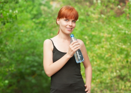 Fitness woman drinking water from bottle outdoors photo
