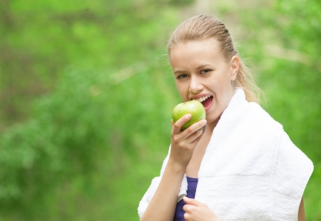 Young beautiful caucasian woman after sport workout eating apple outdoors photo