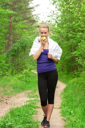 runner girl: Young beautiful caucasian woman after sport workout eating apple outdoors