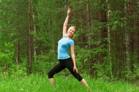 physical activity: Young beautiful woman doing yoga meditation exercise in forest outdoors