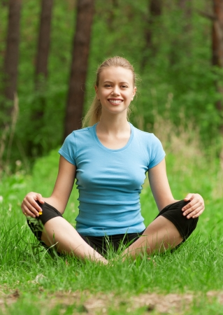 Young beautiful woman doing yoga meditation exercise in forest outdoors photo