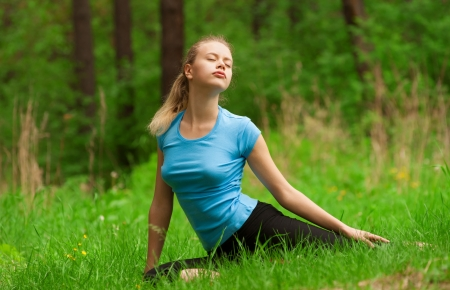 one eye closed: Young beautiful woman doing yoga meditation exercise in forest outdoors