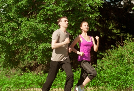 Young beautiful athlete woman and young man jogging in park  photo