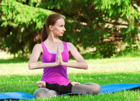 Young beautiful woman doing yoga meditation exercise outdoors photo