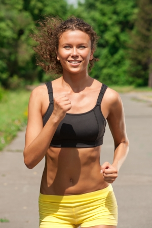 Young beautiful athlete woman jogging in summer park  photo