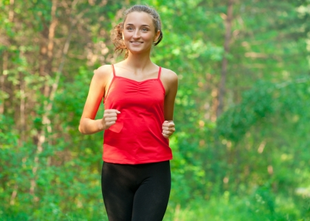 Young beautiful caucasian woman jogging in summer park. Woman in sport outdoors photo