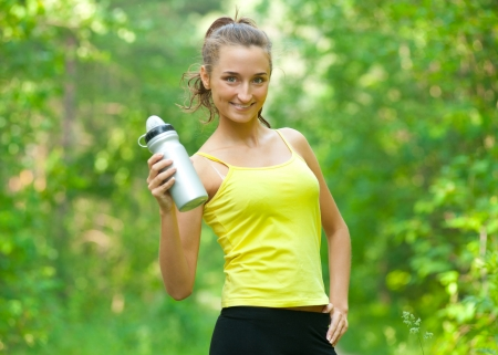Young beautiful woman with bottle of water after fitness exercise outdoors photo