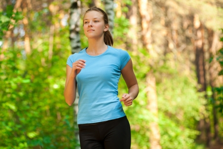 Young beautiful caucasian woman jogging in summer park  photo