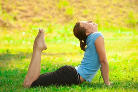 Young beautiful caucasian woman doing yoga meditation exercise on green grass at park photo