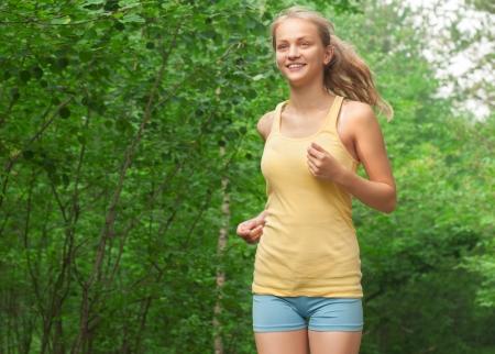 Young beautiful caucasian woman jogging in park  photo