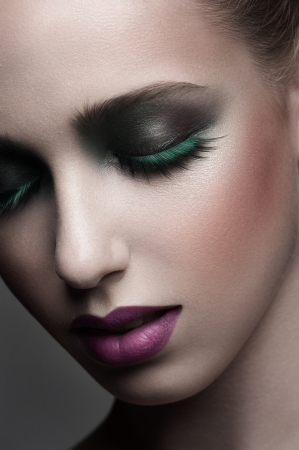 Fashion studio shot of young beautiful woman with stylish bright makeup photo