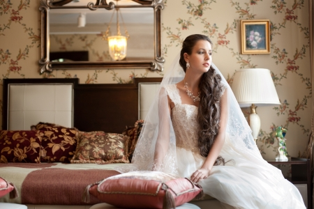 Beautiful bride in elegant wedding dress sitting on bed in her bedroom photo