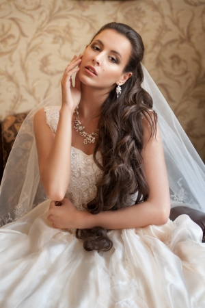 Beautiful bride in elegant wedding dress with long curly hair  photo
