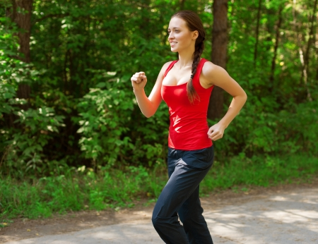 Young beautiful athlete woman jogging outdoors in park  photo