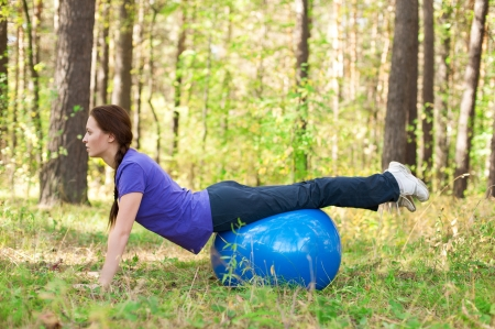 fit ball: Portrait of young fitness woman exercising with a fitness ball outdoors