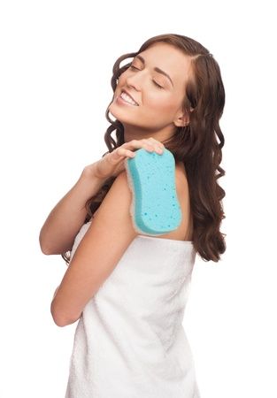 Portrait of young beautiful woman wearing white towel washing with blue bath sponge. Isolated on white background photo